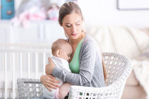 Postpartale Depression: Frau hält traurig ihr Baby im Arm