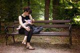 Stillen: Mutter stillt Baby auf der Parkbank