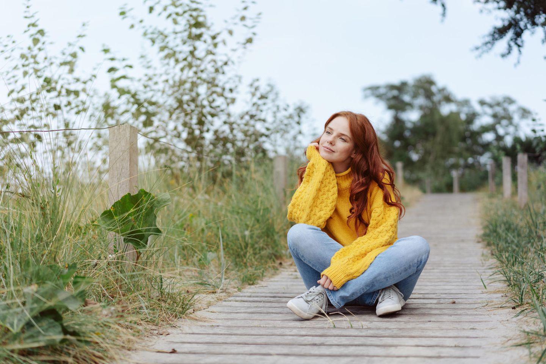 Wie kann ich mir das Leben leichter machen? Hübsche rothaarige Frau sitzt auf einem Steg