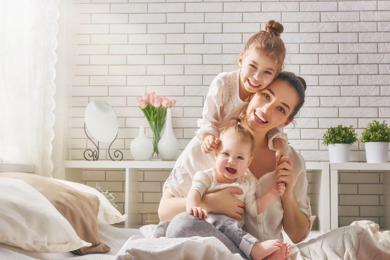 Zweites Kind: Mutter mit zwei Kindern im Bet