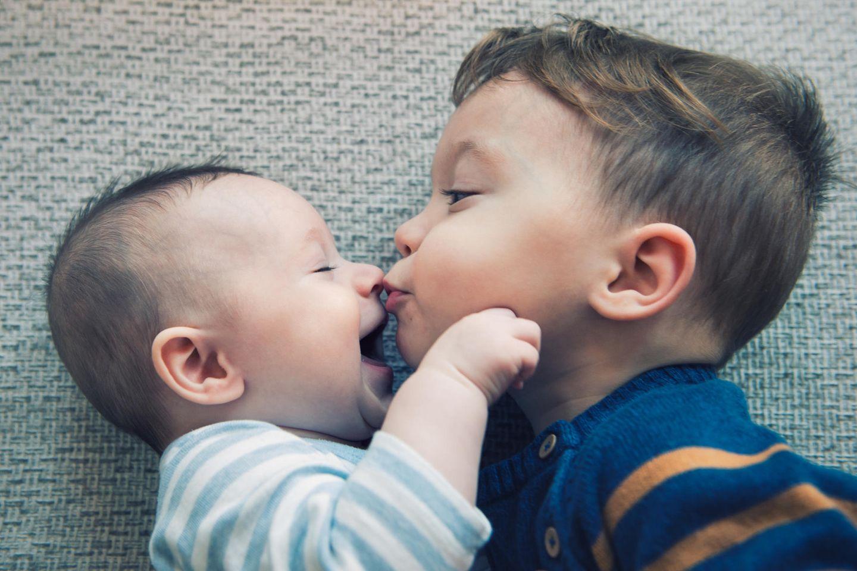 Zweites Kind: Sohn küsst sein Geschwisterchen