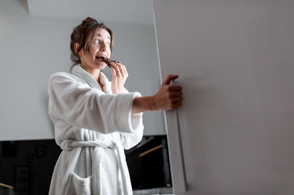 Schlechte Mutter? So ein Quatsch!: Frau isst Schokolade vor dem Kühlschrank