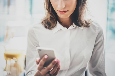 Frau schaut auf Smartphone