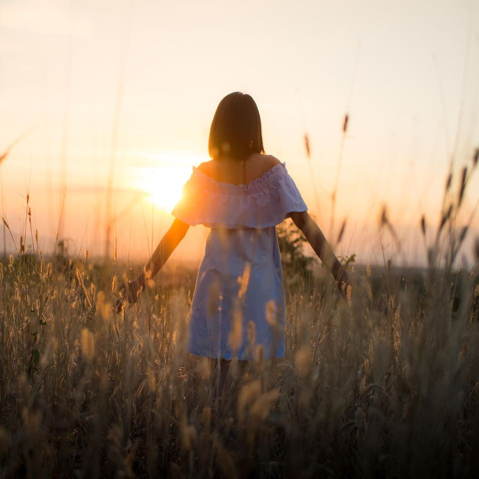 Neurologie: Eine Frau auf einem Feld im Sonnenuntergang