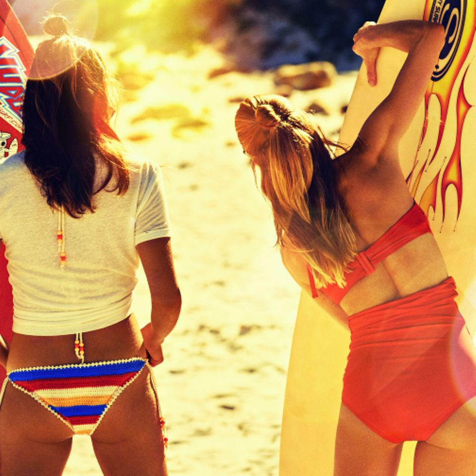 Haarpflege im Sommer: zwei Mädchen am Strand mit Surfboard