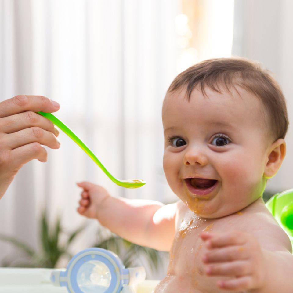 Abendbrei: Baby wird gefüttert und lacht