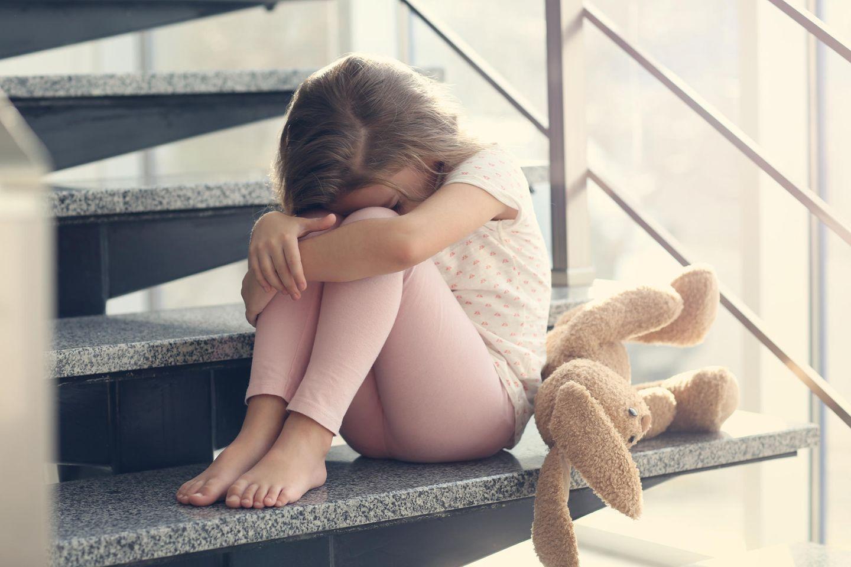 Familienleben: Kind sitzt traurig auf Treppe