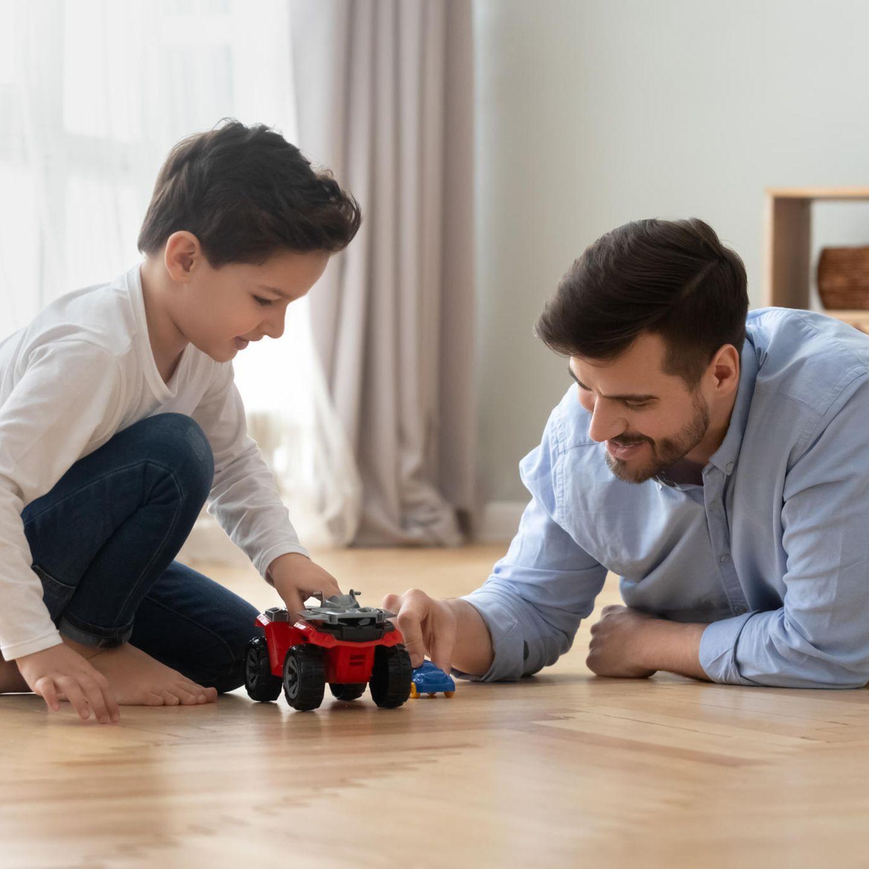 Onkel spielt mit Junge Auto