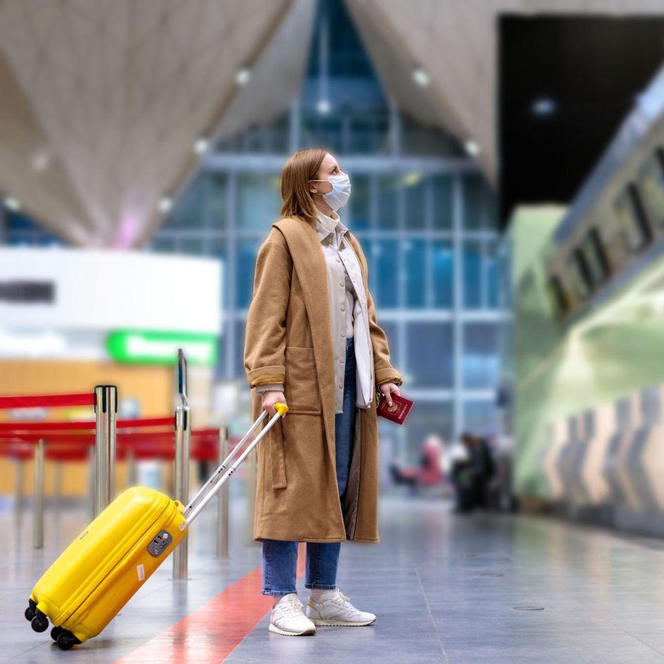 Corona aktuell: Eine Frau mit Mundschutz am Flughafen