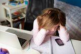 Medienerziehung: Kind mit Laptop und Handy bei den Hausaufgaben