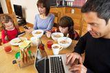 Medienerziehung: Familie mit Handy, Laptop und Co. am Esstisch