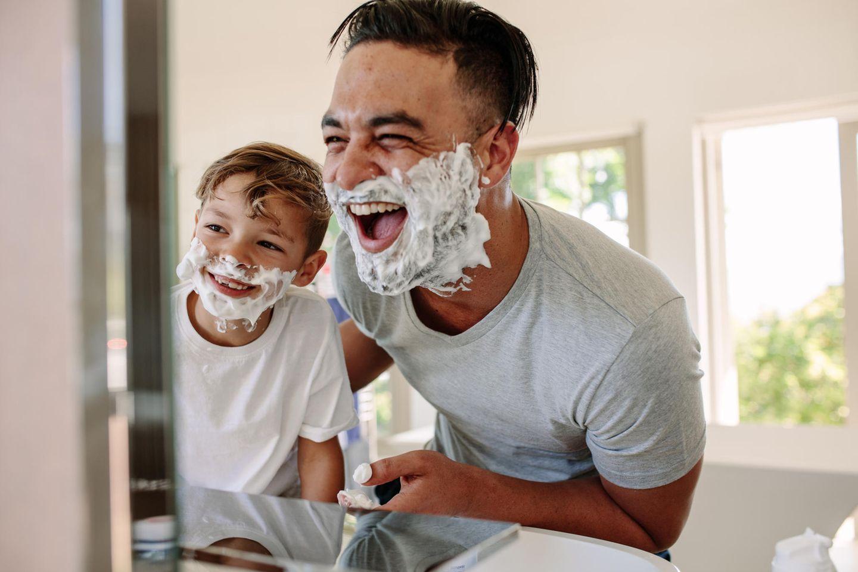 Papa und Sohn lachen beim rasieren