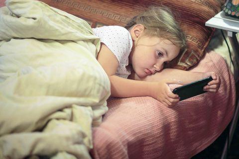 Medienerziehung: Kind mit Handy im Bett