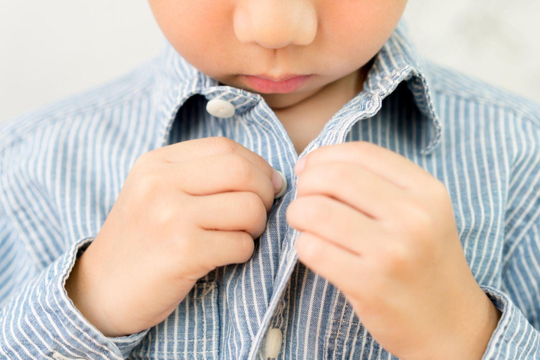 Familienleben: Junge knöpft sich sein Hemd zu
