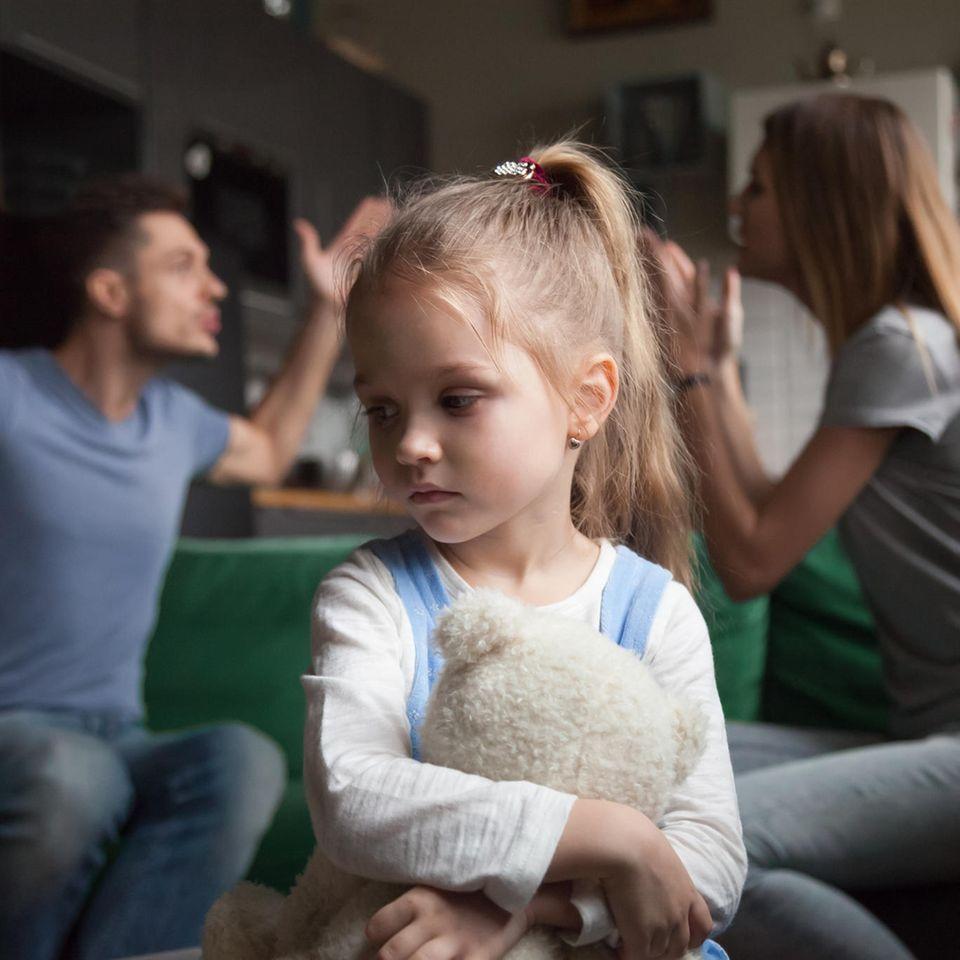 trauriges Mädchen vor streitenden Eltern