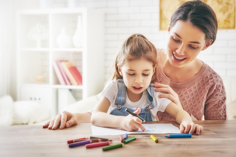 Kind malt mit Mutter