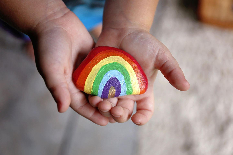 Kind hält regenbogenfarbigen Stein in den Händen