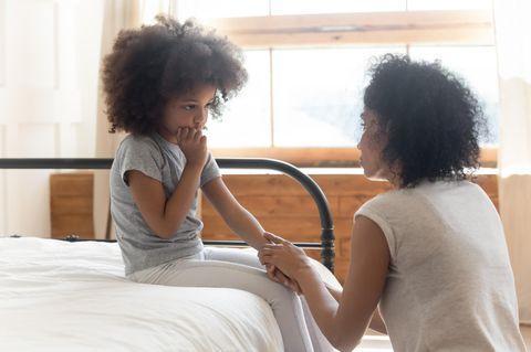 Trauriges Kind sitzt mit Mama auf Bett