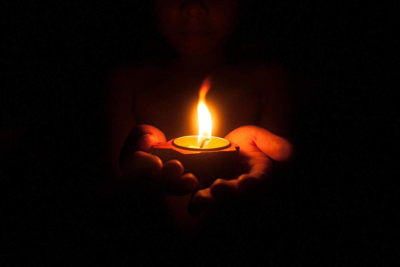 Kind mit Kerze in den Händen