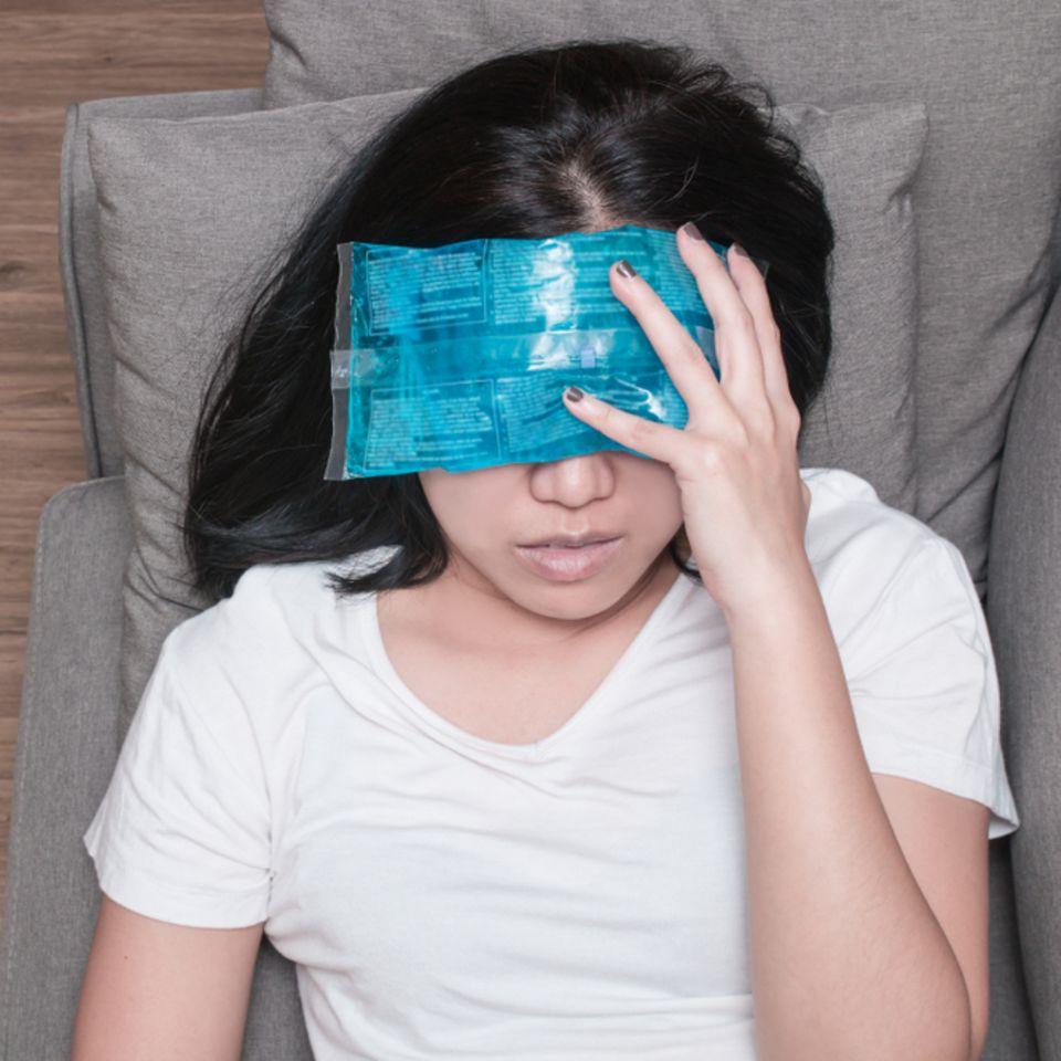Migräne: Frau mit Tuch auf der Stirn