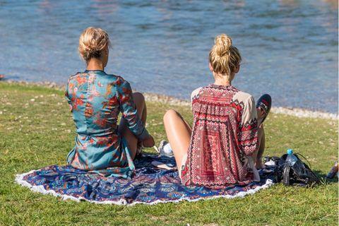 München: Zwei Frauen sitzen am Kanal
