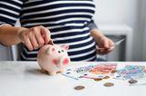 Mehr Geld für die Familie: Schwangere mit Sparschwein