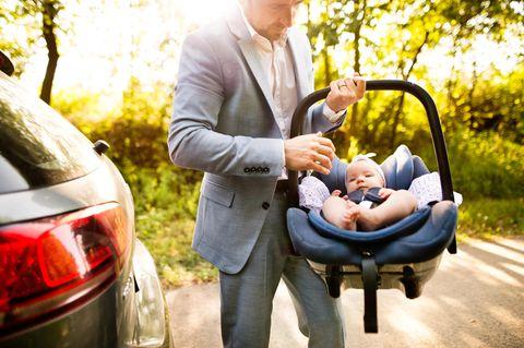Väter-Fitness im Babyalltag: Vater trägt Baby in Autositz