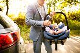 Väter-Fitness im Babyalltag: Papa trägt Baby im Autositz
