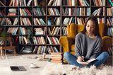 Leseecke einrichten: Frau sitzt vor Bücherregal
