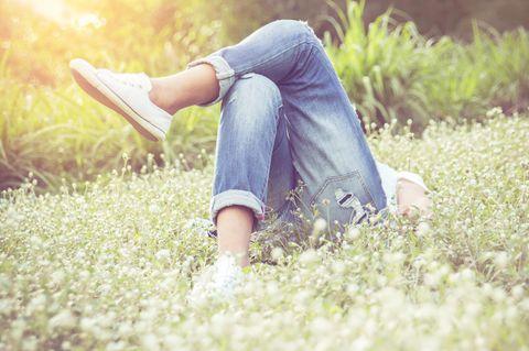 Besser mit Gefühlen umgehen: Eine Frau liegt auf einer Wiese