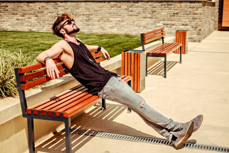 Womanizer enthüllt vier Geheimnisse über Aufreißer: Ein attraktiver Mann sitzt auf einer Bank