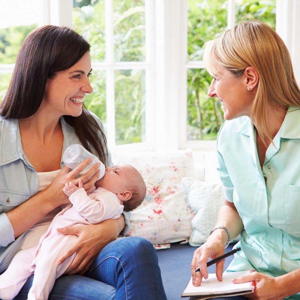 Nachsorge: Hebamme spricht mit Mutter