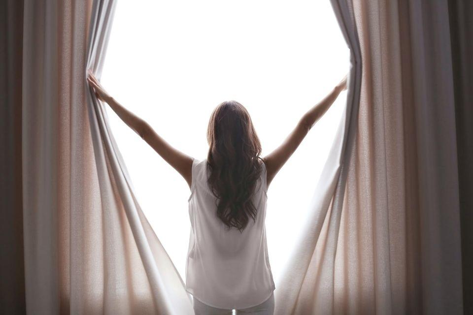 Vorhänge tagsüber schließen: Frau vor Vorhängen