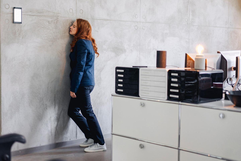 Frau schläft an Wand gelehnt in Büro