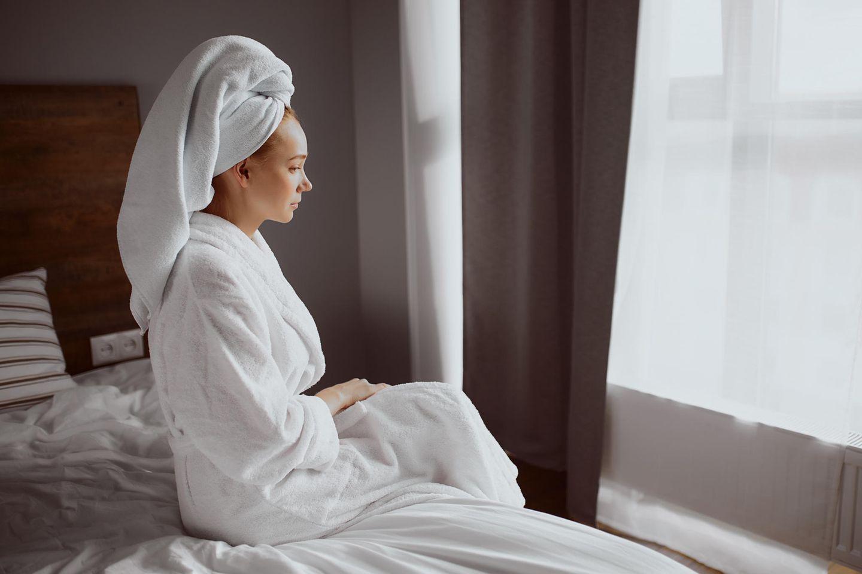 Seelische Belastungen: Bedrückte Frau im Bademantel