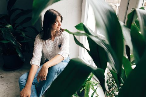 Raumklima verbessern: Frau sitzt zwischen Pflanzen