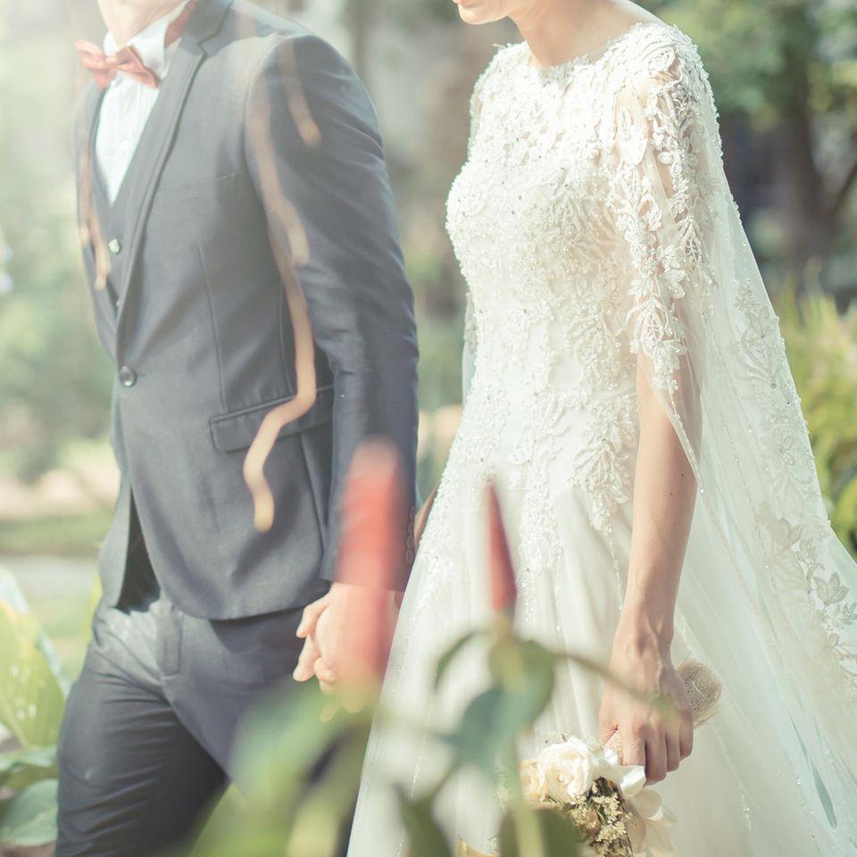 Whisper: Ein Brautpaar geht Hand in Hand spazieren