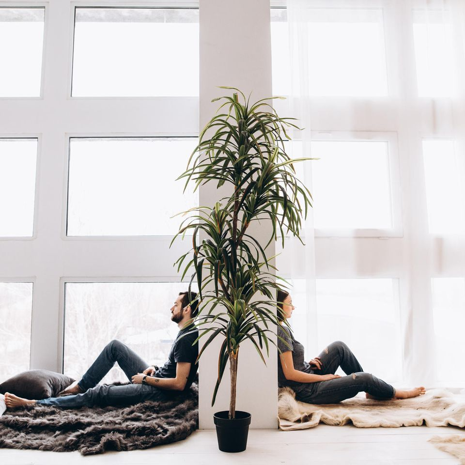 Beziehungsleben: Paar sitzt getrennt voneinander an Wand