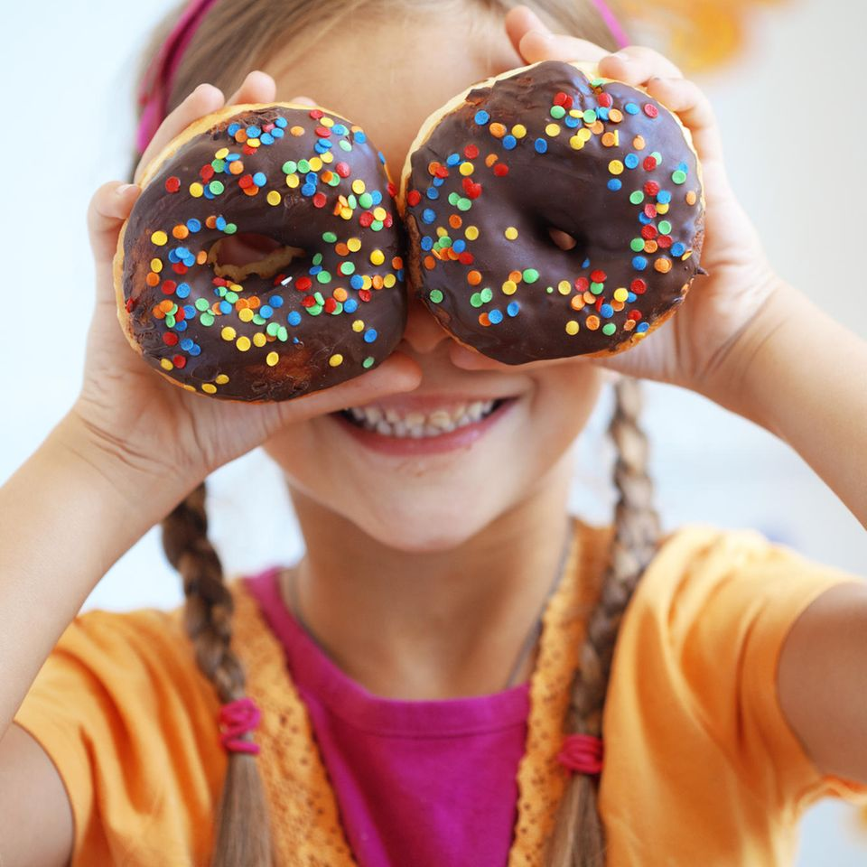 Kinderlebensmittel: Kind mit Donuts