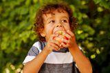 Kinderernährung: Kind beißt in einen Apfel