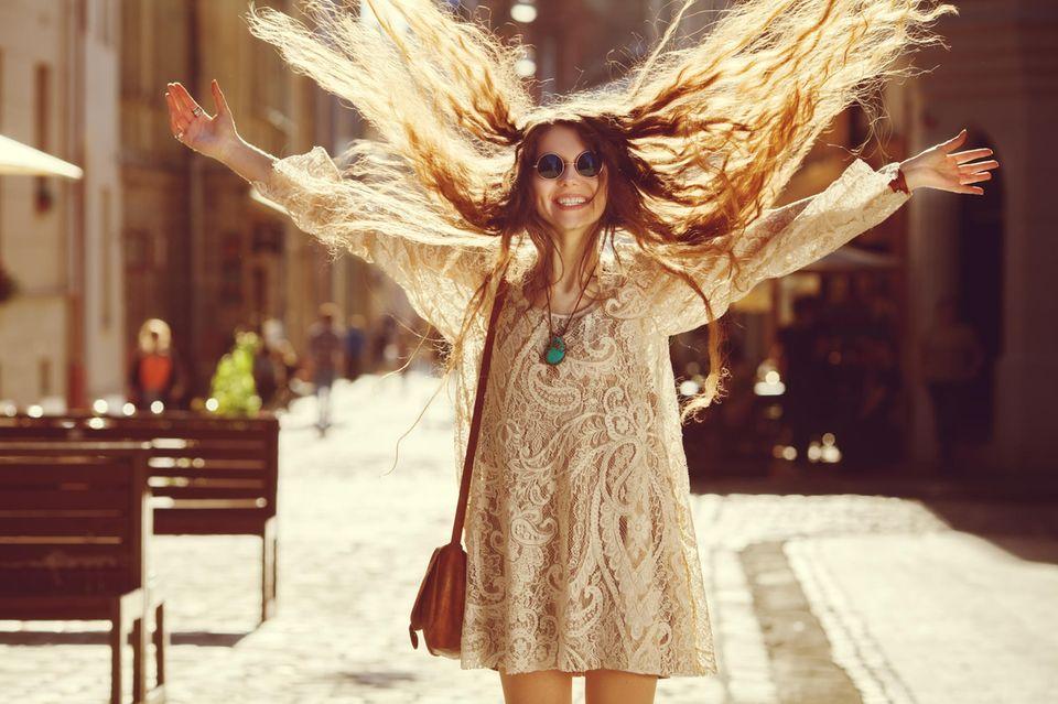 Horoskop: Eine fröhliche Frau wirft ihre Haare in die Luft