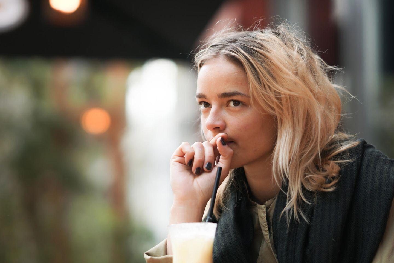 Curving: Eine junge, nachdenkliche Frau mit einem Drink