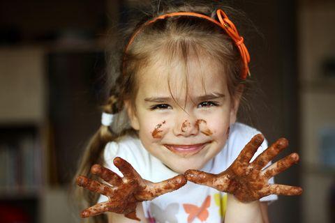 Körbchen-Trick: Mädchen zeigt Hände voller Schokolade