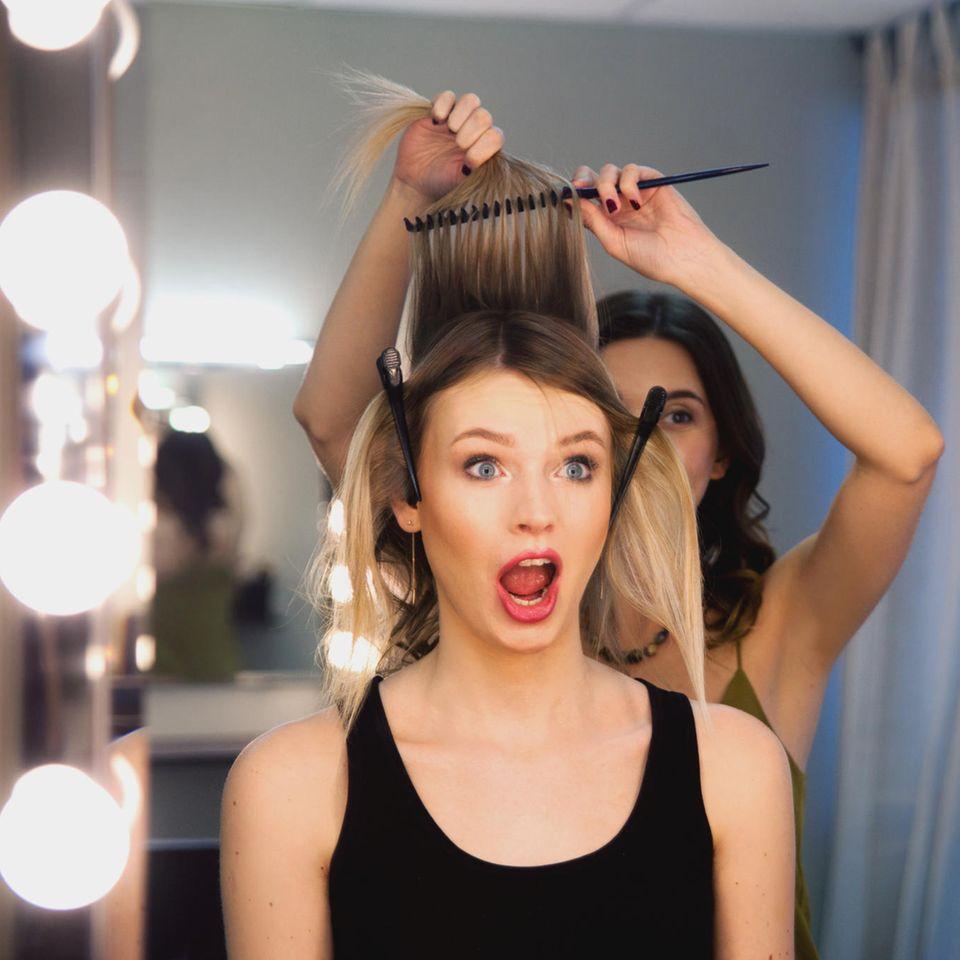 Fehler vor einem Friseurbesuch: Frau vor dem Spiegel