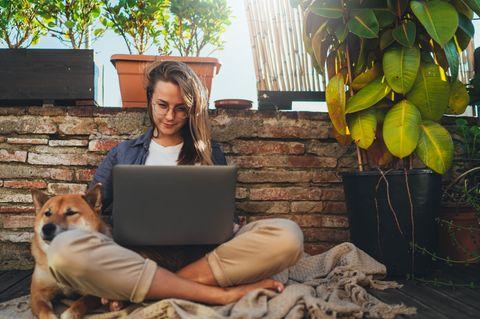 Warum sind manche Menschen so gelassen? Eine entspannte Frau mit Laptop und Hund auf ihrem Balkon