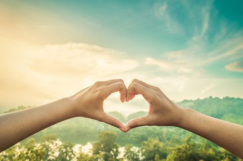 Hände formen ein Herz vor schöner Landschaft