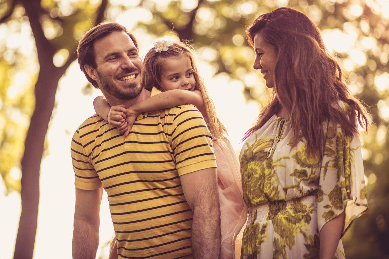 Einzelkind: Mutter und Vater mit Kind auf dem Rücken