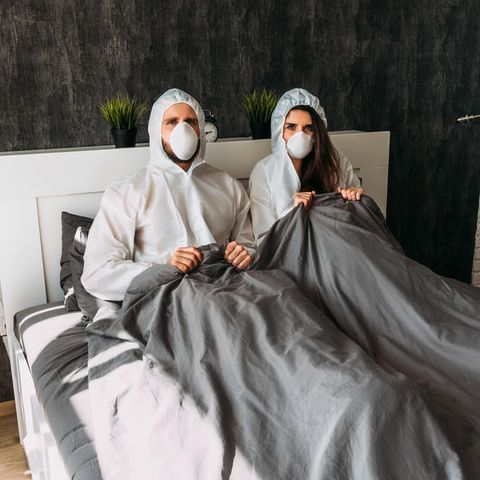 Corona aktuell: Paar mit Schutzmontur im Bett