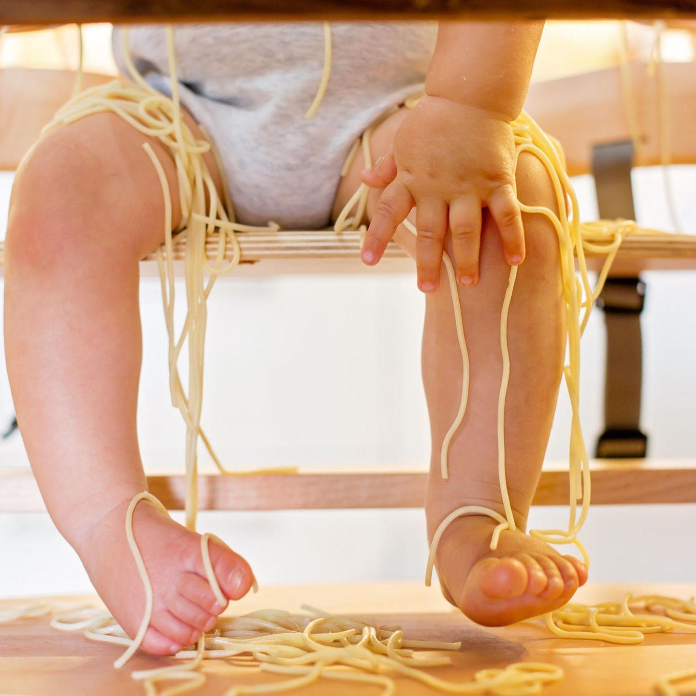 Absurde Elternsprüche: Kleinkind inmitten von Nudeln