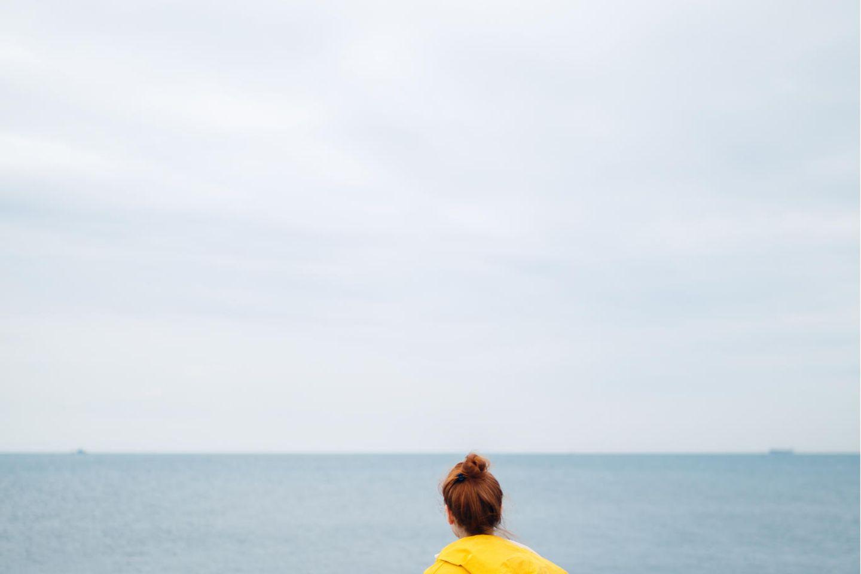 Warum finden Frauen schwerer einen neuen Partner: Frau sitzt alleine am Meer